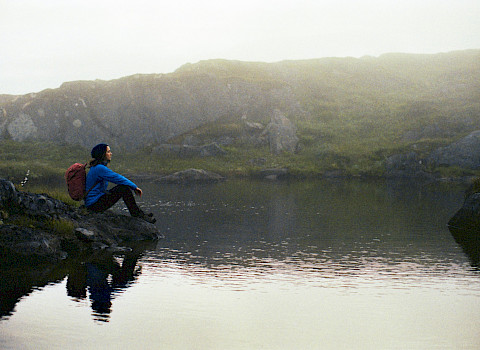 Woman sitting at a lake in Northern Norway